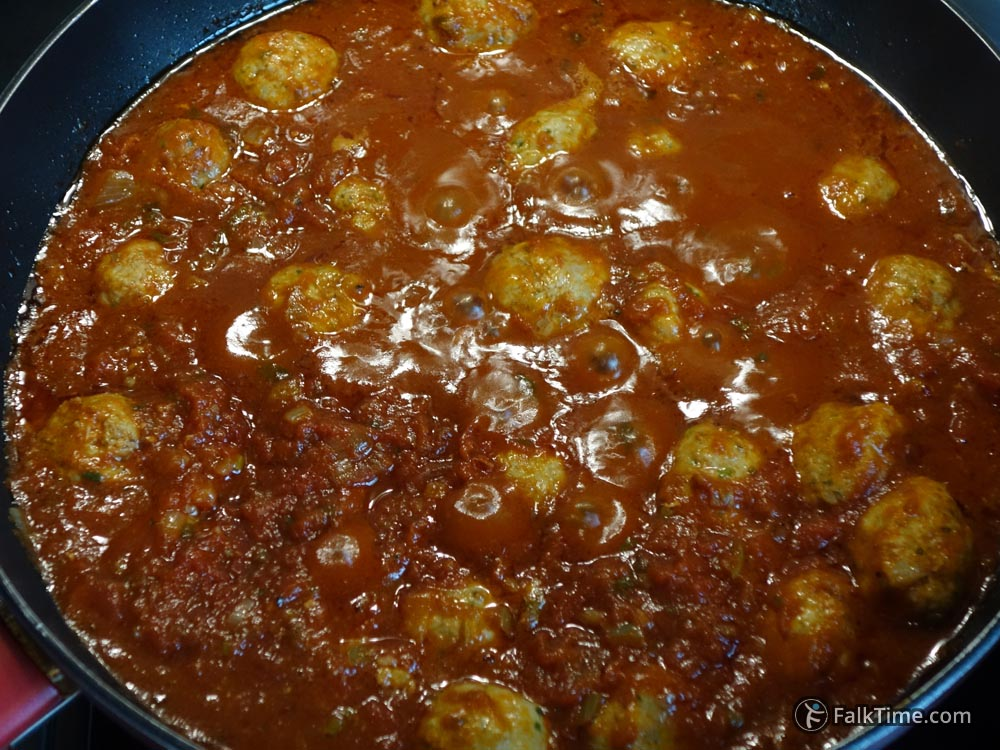 Placing meatballs in tomato sauce